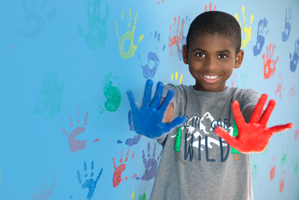 Boy hand painting a wall